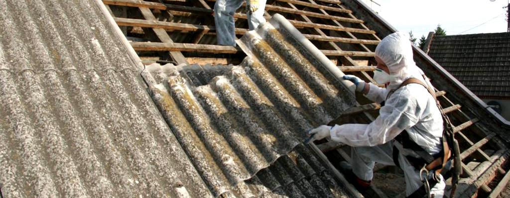 Dach z pokryciem azbestowym i pracownik w ubraniu ochronnym zdejmujący płytę falistą azbestową.