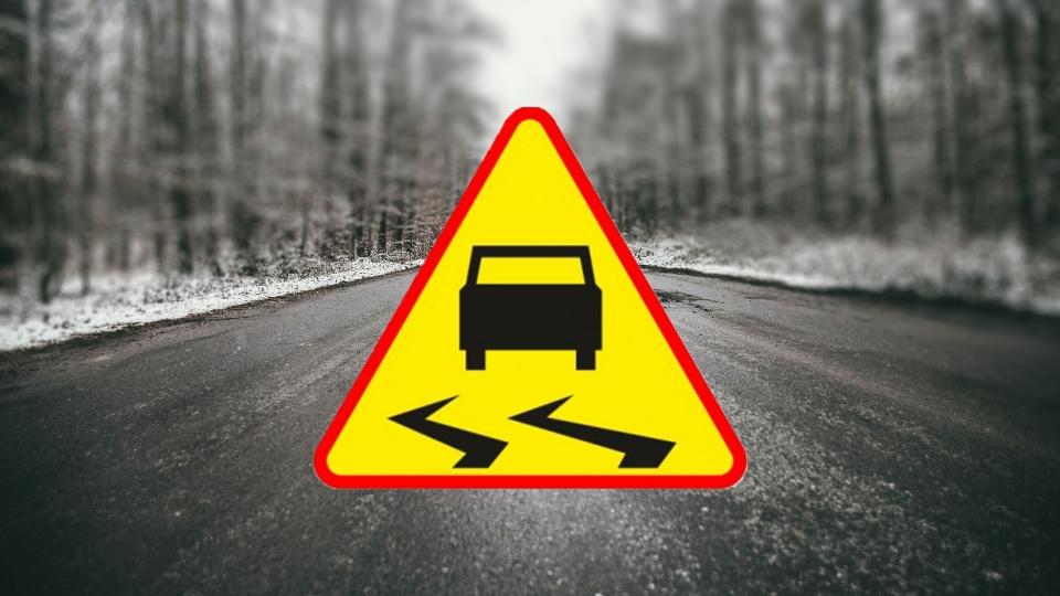 znak ostrzegawczy śliska nawierzchnia na tle zdjęcia drogi